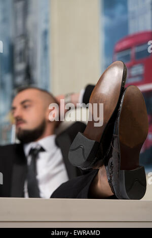 Relaxed Businessman Kicks Back With His Feet Up - Stock Photo