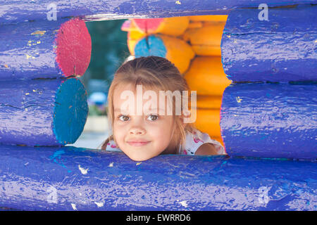 Five-year girl playing on the playground looks out from a wooden window - Stock Photo