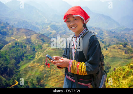 Hmong girl tour guide on her cell phone in Sapa, Vietnam above rice paddy. - Stock Photo