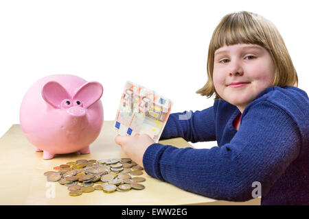Young girl showing euro money notes and coins for piggy bank isolated on white background - Stock Photo