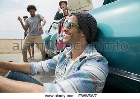 Friends hanging out around convertible at beach - Stock Photo