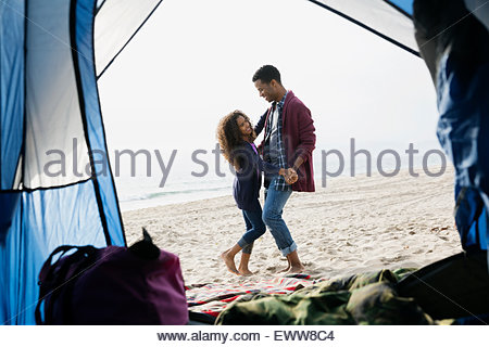 Father and daughter dancing on beach outside tent - Stock Photo