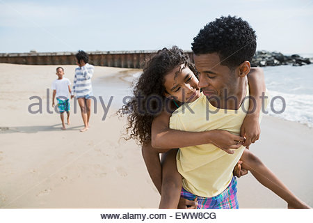 Father piggybacking daughter on beach - Stockfoto