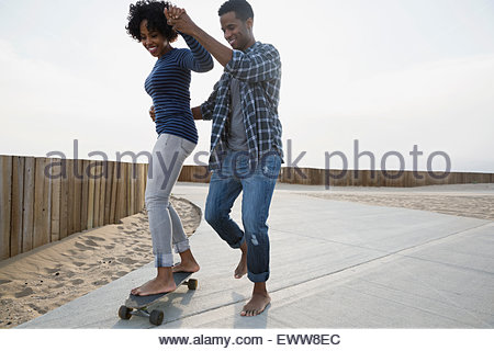 Couple skateboarding on beach path - Stock Photo