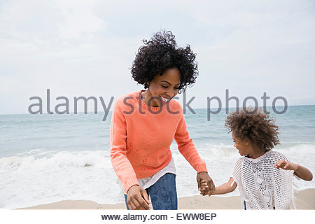 Smiling mother and daughter holding hands on beach - Stockfoto