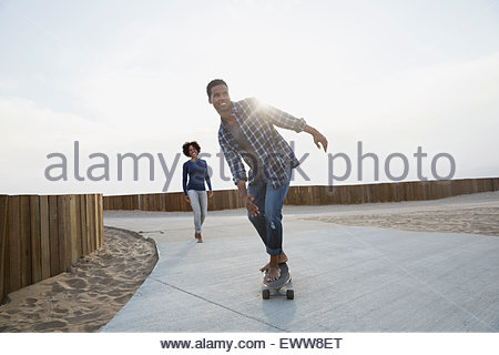 Man skateboarding on beach path - Stock Photo