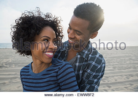 Affectionate couple hugging on sunny beach - Stockfoto