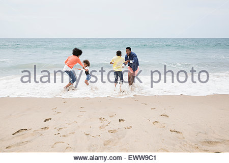 Family playing in ocean at beach - Stock Photo