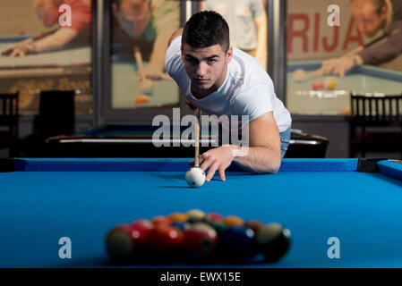Young Man Lines Up A Shot - Stock Photo