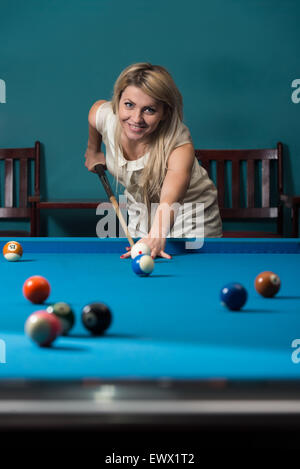 Young Women Lines Up A Shot - Stock Photo