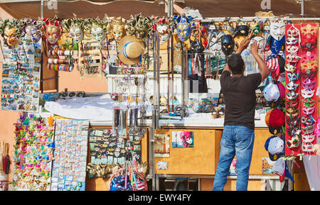 Stall holder putting carnival masks on display Burano Venetian Lagoon Veneto Italy Europe - Stock Photo