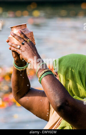 Hindu woman immersed in the holy, but polluted, Ganges water, raises a container of the sacred water at a bathing - Stock Photo