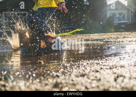 Boy jumping in puddle of muddy water - Stock Photo