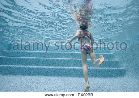Girl swimming underwater in swimming pool, rear view - Stock Photo