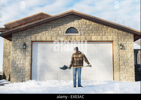 Man shoveling snow, Young's Point, Ontario, Canada - Stock Photo