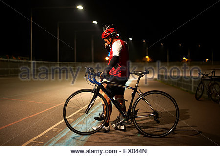 Cyclist standing by track with bike at velodrome - Stock Photo