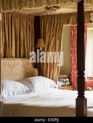 Georgian four poster bed in bedroom with toile de jouy curtains - Stock Photo