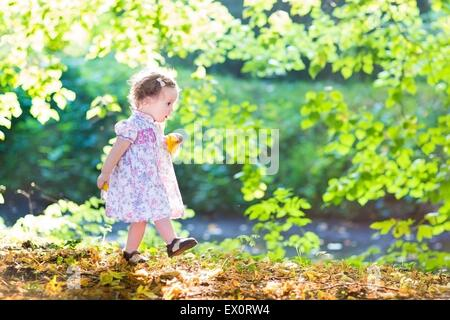 Beautiful baby girl in a pink dress walking next to a river on a very sunny warm autumn day - Stock Photo