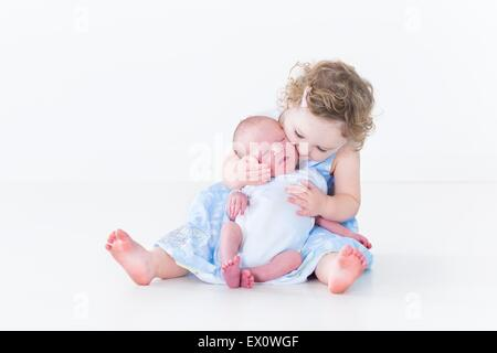 Sweet toddler girl kissing her newborn baby brother - Stock Photo