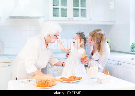 Funny toddler girl playing in a kitchen, having fun baking an apple pie with her grandmothers - Stock Photo