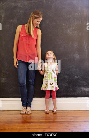 Full length shot of sweet little girl standing with her mother at home. Mother and daughter looking at each other - Stock Photo