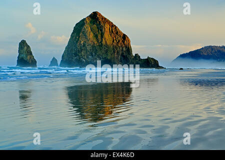 Haystack Rock wider auf Wasser und Wellen, Cannon Beach, Oregon USA - Stockfoto