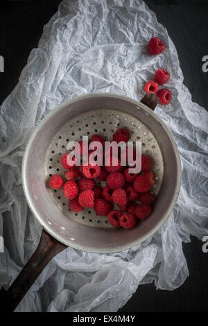Raspberries in vintage colander on black slate background and white paper. Top view - Stock Photo