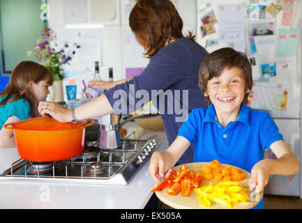 Smiling Boy Holding Chopping board with Vegetables, Family in background - Stock Photo
