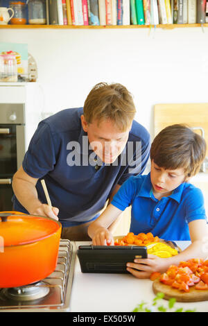 Father and Son Cooking Using Digital tablet in Kitchen - Stock Photo
