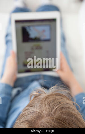 Back View of Young Boy Playing Game on Digital Tablet - Stock Photo