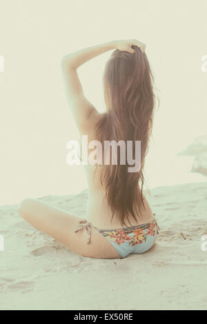 Back View of Young Woman Sitting on Beach - Stock Photo