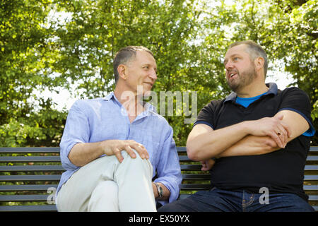Two Men Sitting on Park Bench Talking - Stock Photo