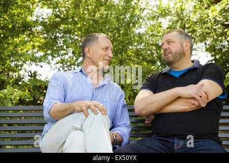 Two Men Sitting on Park Bench Talking - Stock Photo