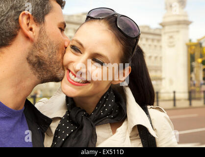 Man Kissing Woman on Cheek - Stock Photo