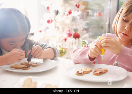 Two Young Girls Decorating Ginger bread man Biscuits - Stock Photo