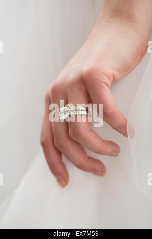 Bride wearing wedding dress and engagement ring - Stock Photo