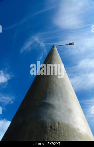 lamp on a high support against the blue sky with clouds - Stock Photo