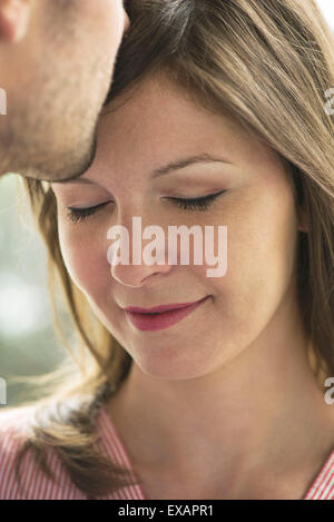 Man kissing woman's forehead, cropped - Stock Photo