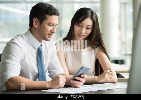 Colleagues looking at smartphone together in office - Stock Photo