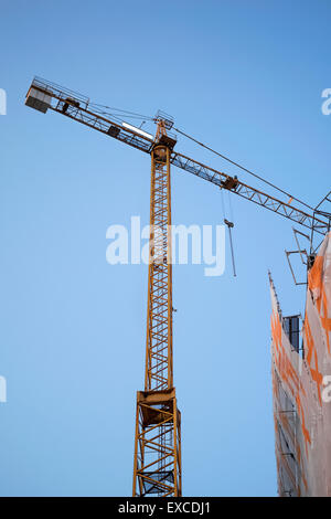 Yellow construction crane on building site with white Ad space on the top against blue sky. - Stock Photo