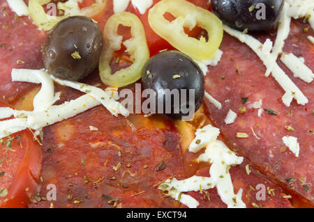 Close up of dark olives and paprika on top of a home baked pizza - Stock Photo