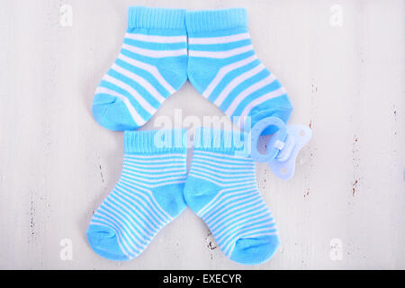 Its a Boy Baby Shower or Nursery concept with socks and pacifier dummy on white shabby chic  wood - Stock Photo