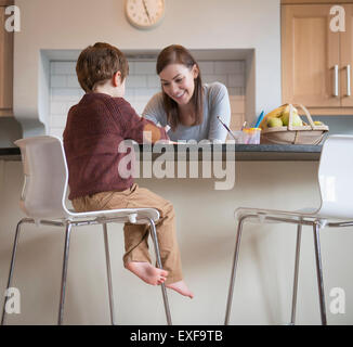 Boy sitting on stool with mother in kitchen and drawing - Stock Photo