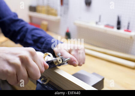 Close up of young female carpenters hands planing timber in workshop vice - Stock Photo