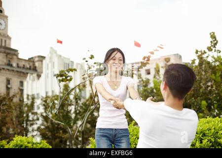 Tourist couple dancing, The Bund, Shanghai, China - Stock Photo