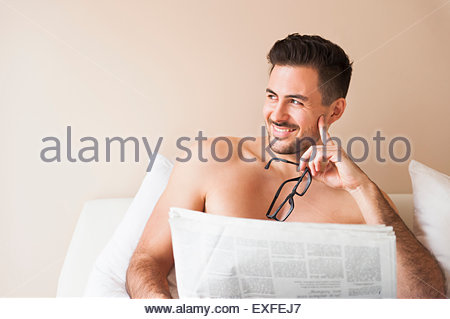 Young man sitting up in bed reading newspaper - Stock Photo