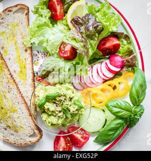 Plate with bread and fresh vegetables for vegan breakfast/lunch. Top view. - Stock Photo