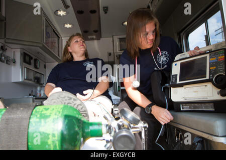 Female paramedics working in the back of an ambulance. Rural volunteer US fire department. - Stock Photo