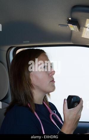Female paramedic EMT using radio in ambulance. Rural volunteer fire department ambulance. - Stock Photo