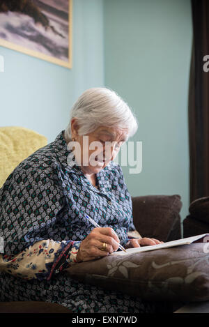 Senior woman doing crossword puzzle at home - Stock Photo